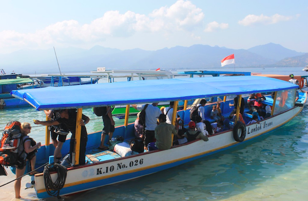 Public boat with people in the water on Gili Air