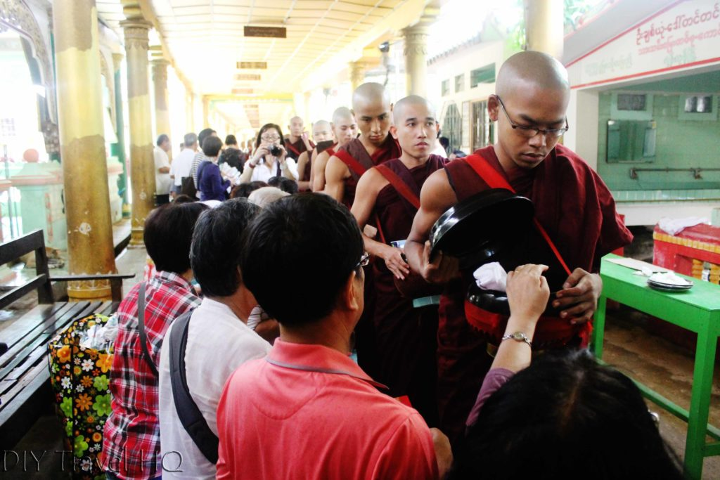 Visitors offering monks rice