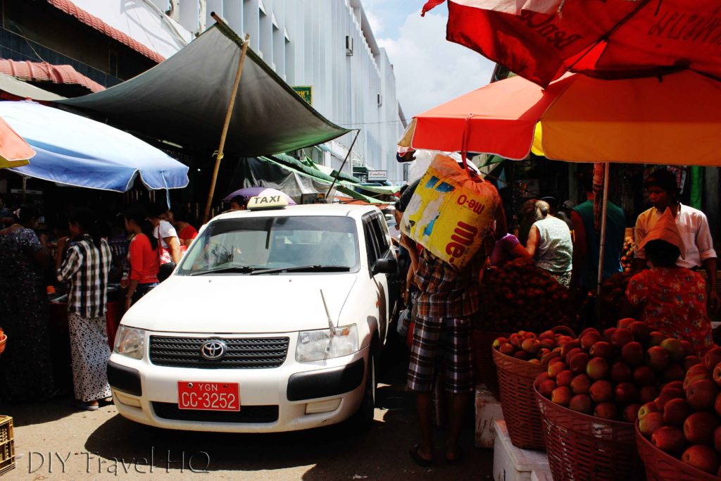 Cars & people squeeze through market