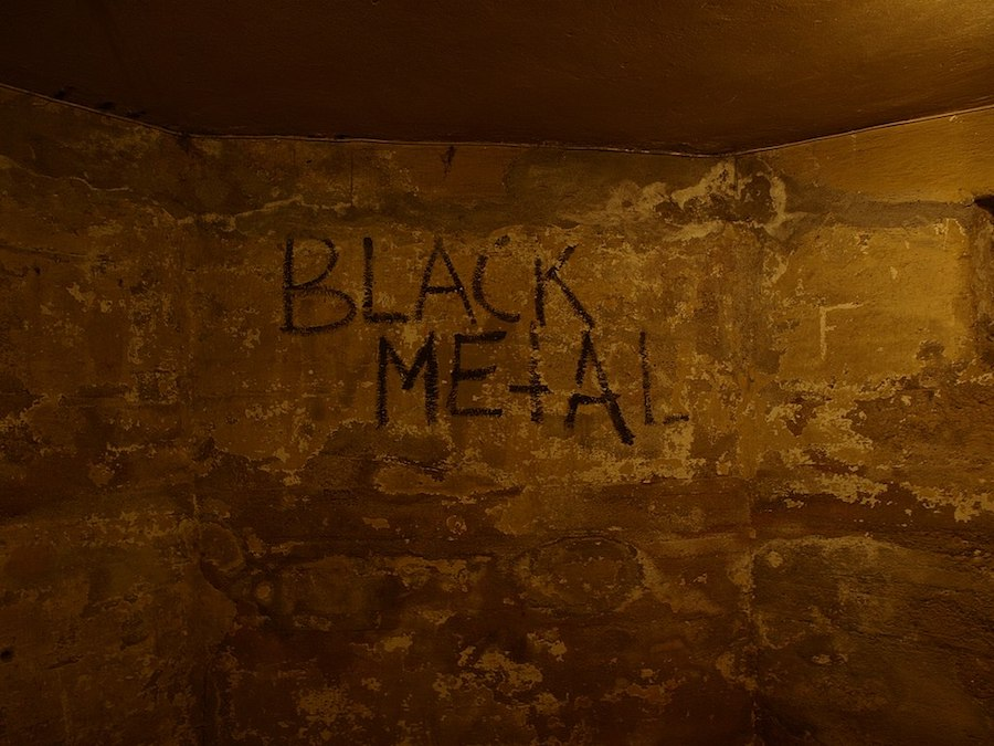 'Black Metal' graffiti on grungy brown wall