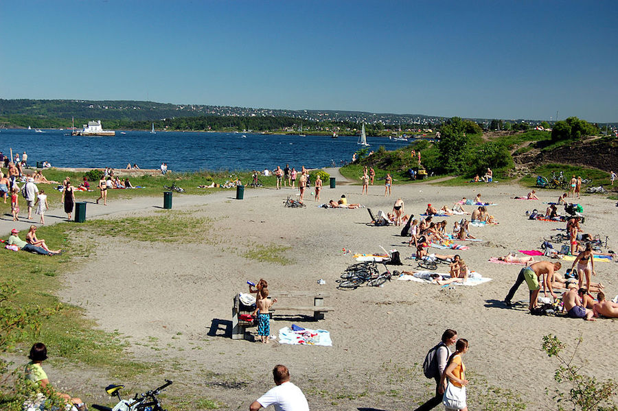 Many people in sand and water at Huk Beach