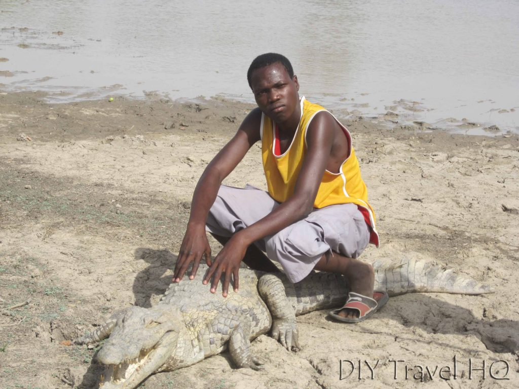 African man sitting on crocodile