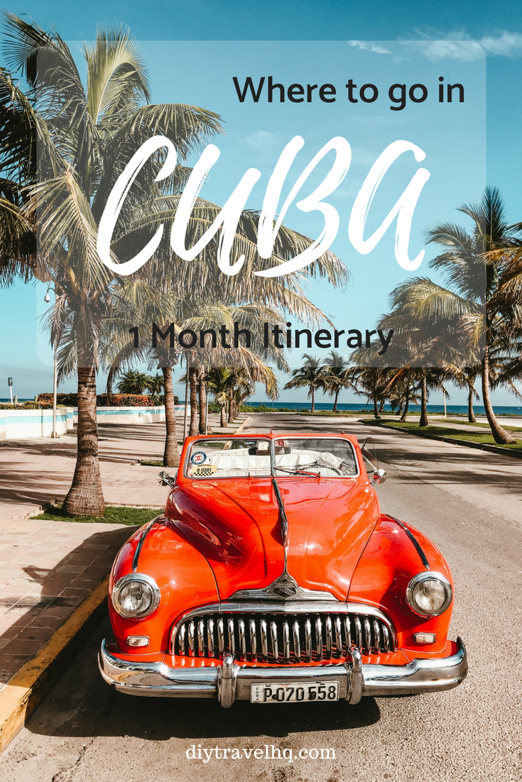 Old classic red car on road with palm trees near beach in Cuba