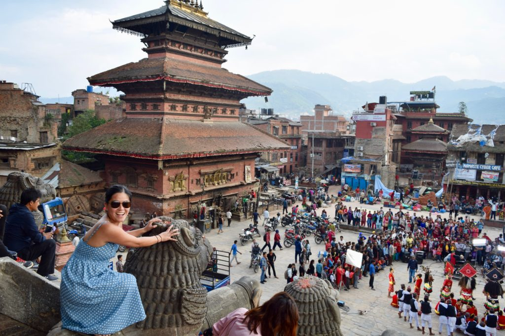Woman on a lion sculpture overlooking Bhaktapur Durbar Square