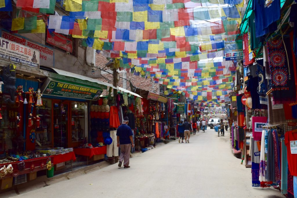 Empty dusty street in Thamel with prayer flags above