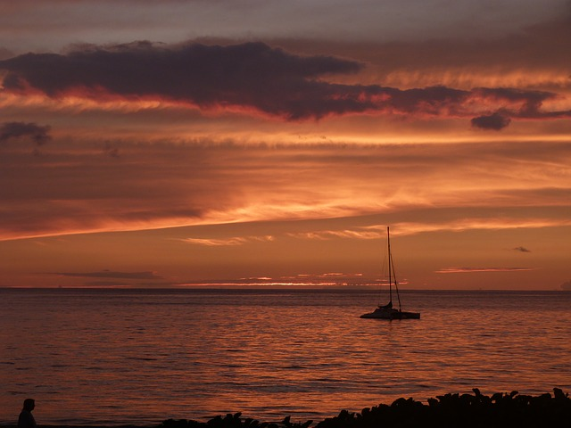 Sail boat in the distance during orange sunset