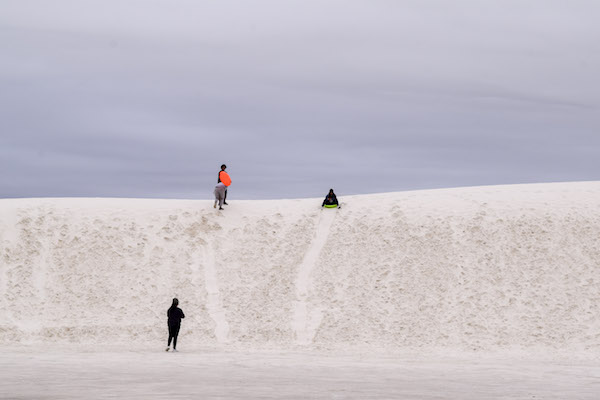 3 people sledding at White Sands