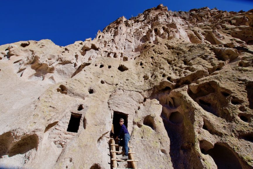Woman climbing ladder into cave hole at Bandelier