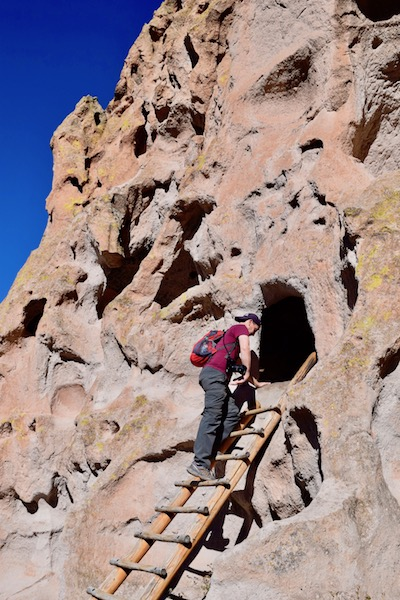 Man on ladder looking to a hole cave at Bandelier National Monument