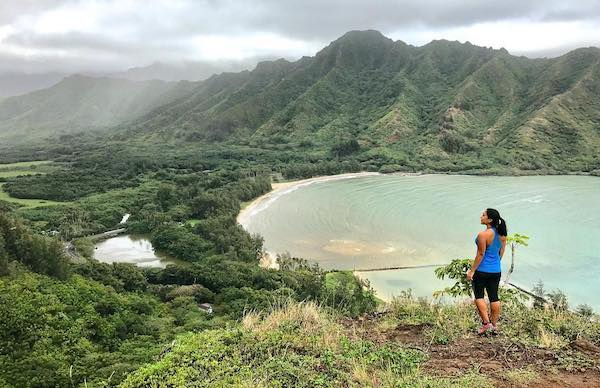 Woman overlooking cove beach surrounded by mountains - unique things to do in Oahu