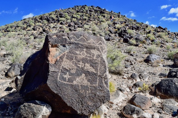 Petroglyphs on big rock with mountain in the background