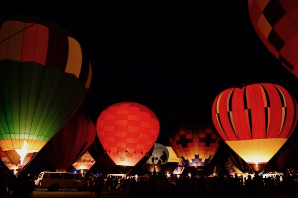 Hot air balloons in lights at night on a field