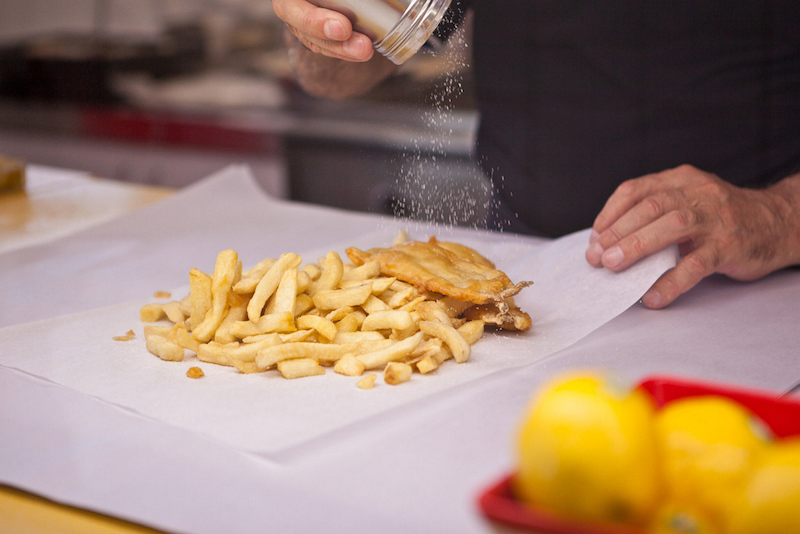 Fish and chips on paper being salted - What to eat in adelaide