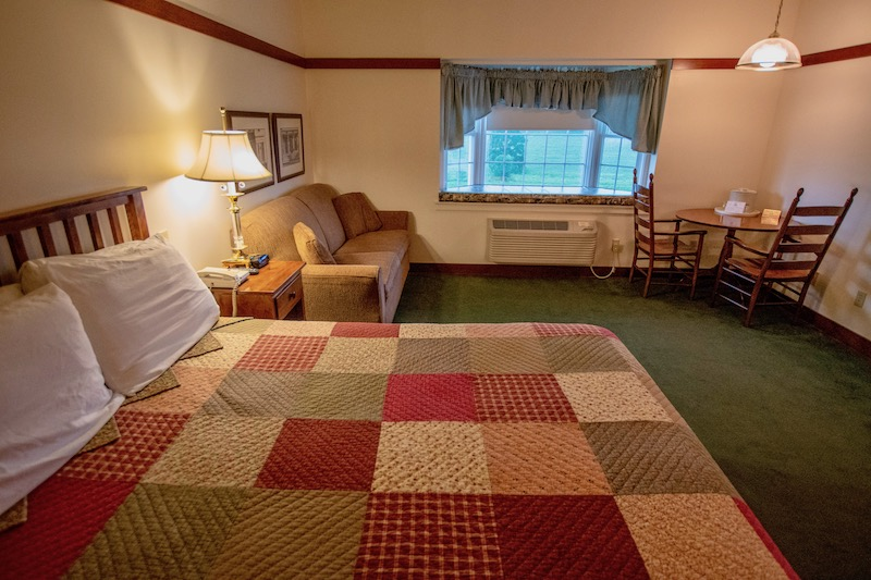 Amish Country lodging hotel room with big kind bed and patchwork quilt