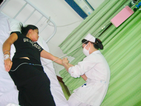 Girl lying in hospital bed with nurse administering IV drip needed budget travel insurance