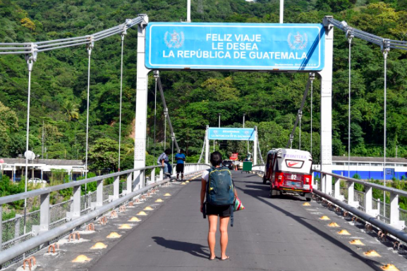 Backpacker travel insurance with girl on a bridge border crossing