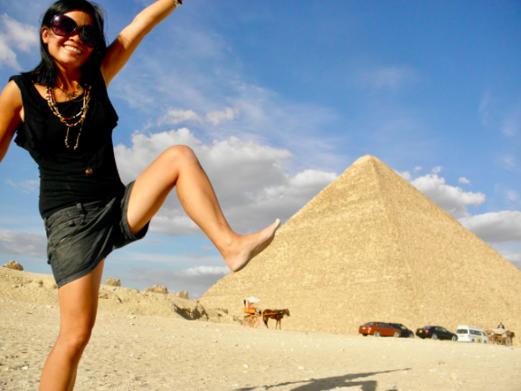 Girl stepping on pyramid photo illusion for Backpacker Travel Insurance