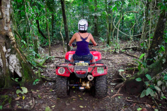Back of girl on ATV in jungle with cheap travel insurance